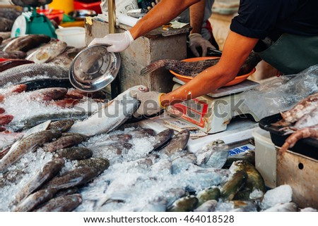 GEORGE TOWN, MALAYSIA - MARCH 23: Man prepare fish for sale at the wet market of Penang on March 23, 2016 in George Town, Malaysia.