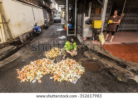 George Town, Penang, Malaysia - 20 April 2013: Chinese burning a ghost money in front of his shop in George Town on April 20.