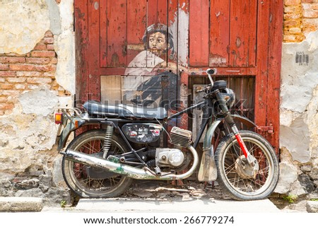 GEORGE TOWN,PENANG ,MALAYSIA- CIRCA March 26, 2015: Public street art Boy on a Bike  on the wall by Lithuanian artist Ernest Zacharevic in Georgetown, Penang, Malaysia. - stock photo