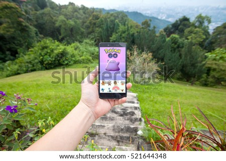 George Town, Penang - November, 2016: Close up view of a person holding a cellphone playing pokemon go. On the screen is registering Pokemon Ditto into pokedex