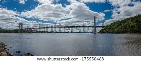 George Washington Bridge spans Hudson River and connects New York and New Jersey. Panoramic view spanning from New Jersey palisades across to NY Upper West Side, with Manhattan skyline (background). - stock photo