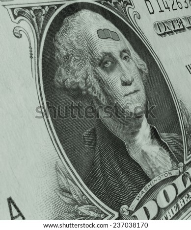 George Washington on a dollar bill is sporting a black eye and a band-aid, as the weak dollar takes a beating.