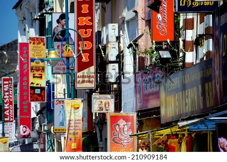 Georgetown, Malaysia - January 8 2007:  A melange of signs hang from storefronts on Lebuh Pasar in Little India - stock photo
