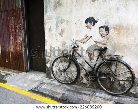 """Georgetown, Penang, Malaysia - April 24, 2014: """"Little Children on a Bicycle"""" street art mural by Lithuanian artist Ernest Zacharevic in George Town, Penang, Malaysia.  - stock photo"""