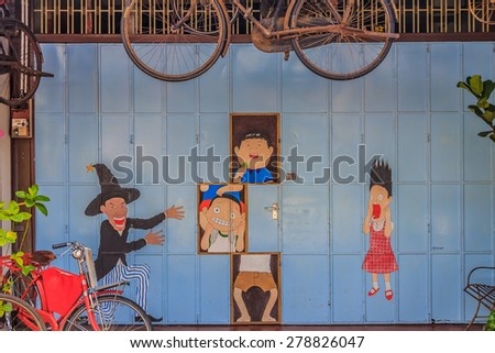"Georgetown, Penang, Malaysia - August 23, 2013: Wall artwork named ""Magic"" in Lebuh Armenian in Penang Georgetown UNESCO heritage zone by Lithuanian artist Ernest Zacharevic"