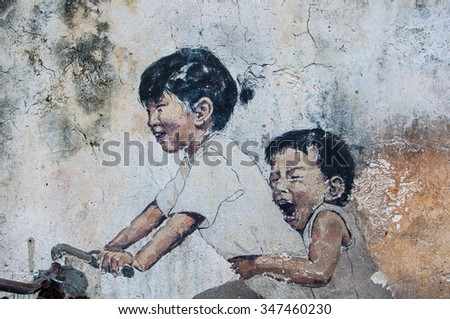 """Georgetown, Penang, Malaysia - February 18, 2015: """"Little Children on a Bicycle"""" street art on wall by Lithuanian artist Ernest Zacharevic in George Town, Penang, Malaysia. - stock photo"""