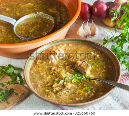 Georgian beef-walnut soup Kharcho with rice, onion, garlic, parsley, coriander and marigold in ceramic cup with metal spoon on the linen table cloth horizontal  - stock photo
