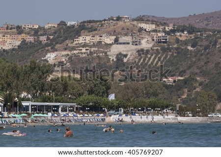 GEORGIOUPOLIS, GREECE - JULY 30, 2013: Beach of Georgioupolis, view from the sea. Georgioupolis - a former fishing village, now a popular holiday destination of tourists from all over Europe