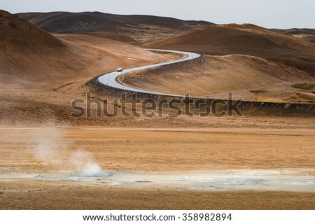 Geothermal mudpot Namafjall with curve road line and mountain range background in Autumn season Iceland - stock photo