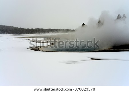 Geothermal pool and geyser in winter Yellowstone National Park - stock photo