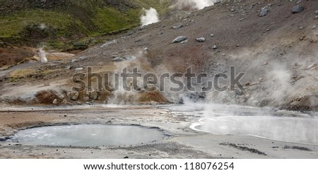 Geothermal water ponds steaming next to rocky slope