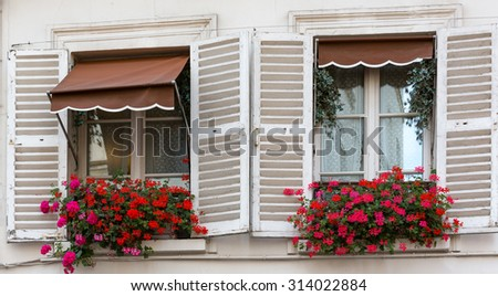 Geraniums fill boxes in French windows, near Paris - stock photo