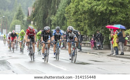 GERARDMER,FRANCE - JUL 12:Group of cyclists including Marcel Kittel and Tom Dumoulin of Team Giant Shimano, riding during a rainy day of Le Tour de France 2014 on July 12, 2014 in Gerardmer - stock photo