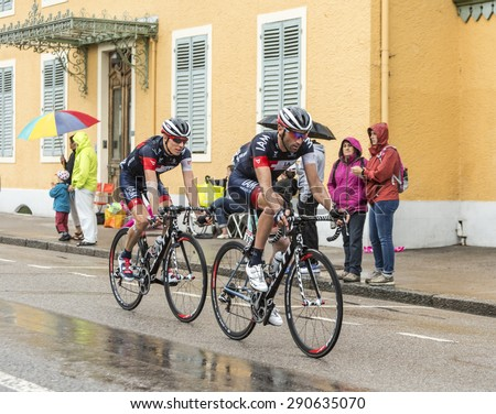 GERARDMER,FRANCE - JUL 12:Two cyclists,Jerome Pineau and Marcel Wyss (IAM Cycling Team) ride during a rainy day the stage 8 of Le Tour de France on July 12, 2014 in Gerardmer - stock photo