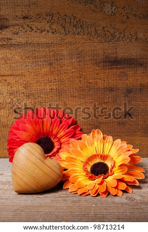 Gerbera and wooden heart in front of a wooden wall. Space for text above.
