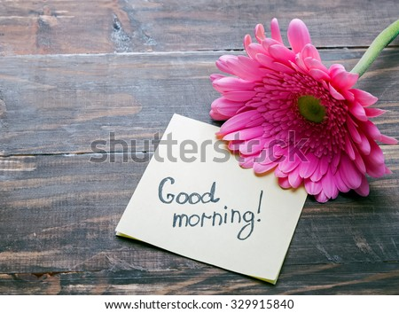 """Gerbera flower and piece of paper with text """"good morning"""" on the wooden table close-up - stock photo"""