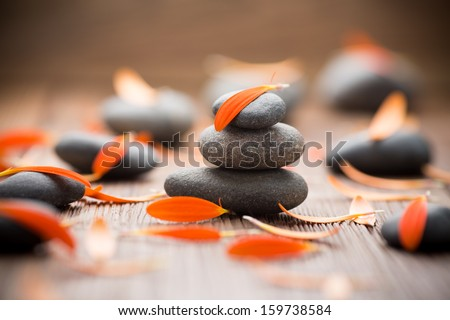 Gerbera flower petals and spa stones, wooden background. - stock photo