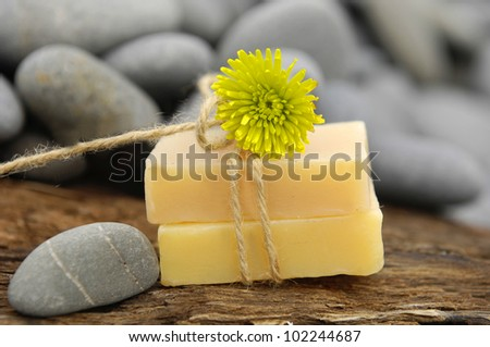 gerbera on soaps and stones on rustic wood