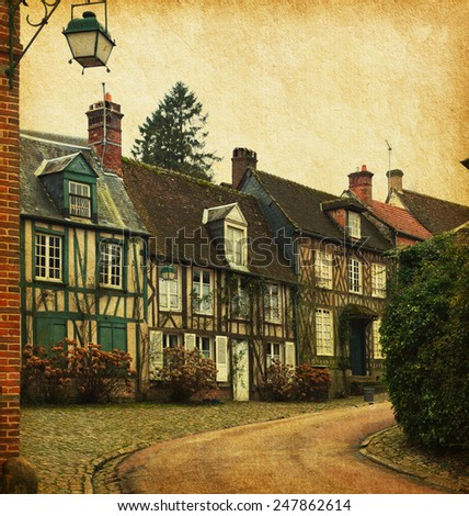 Gerberoy. Old street in medieval village, northern France. Photo in retro style. Paper texture. - stock photo