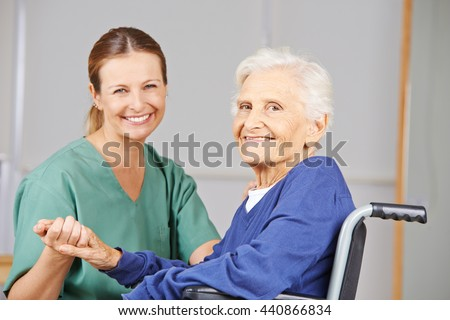 Geriatric nurse and senior woman in wheelchair smiling together in nursing home - stock photo