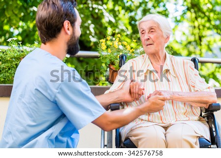 Geriatric nurse holding hand of old woman in rest home - stock photo