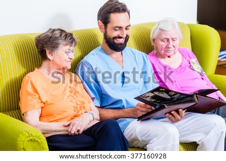 Geriatric nurse looking at pictures with seniors in nursery home - stock photo