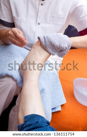 Geriatric nurse washes the foot of a senior - stock photo