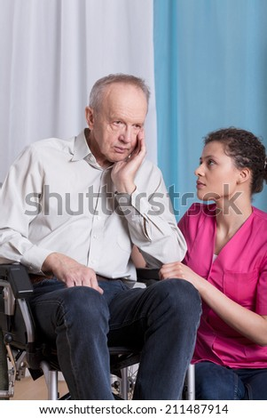 Geriatric patient on wheelchair  talking with nurse - stock photo