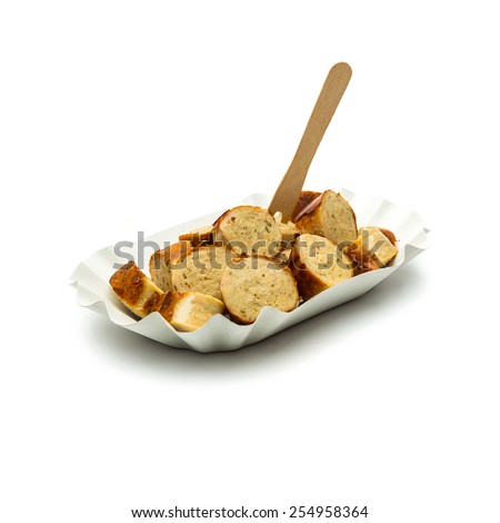 german bratwurst sliced in a paper shell with fork - stock photo