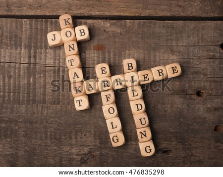 German career concept with the crosswords career, education, job, success and contact on a rustic wooden table