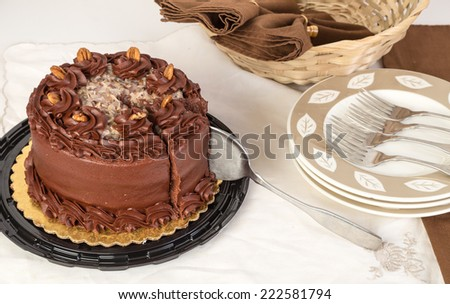 German Chocolate Cake in elegant setting with cake knife cutting a piece. - stock photo