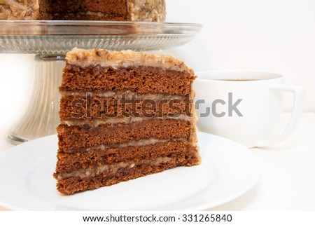 German chocolate cake slice closeup with coffee.  Slice is removed from whole cake which is in background. - stock photo