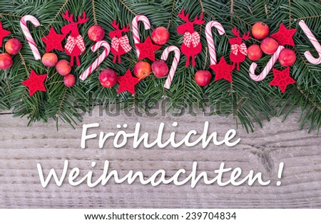 german Christmas card with Pine green, candy Canes, apples and text Merry Christmas/Merry Christmas/german - stock photo