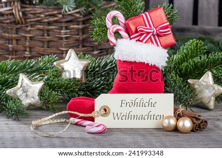 german christmas card with red sock, gifts, Candy canes and text merry christmas/merry christmas/german - stock photo