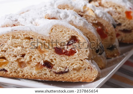 German Christmas fruit bread Stollen sliced macro on a white plate. horizontal