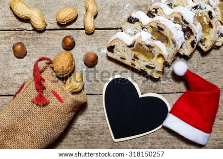 german christmas stollen on a  wooden background, nuts and red hat