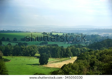 German countryside landscape with creek and green fields - stock photo