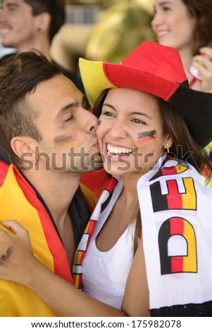 German couple of soccer sport fans kissing celebrating. - stock photo