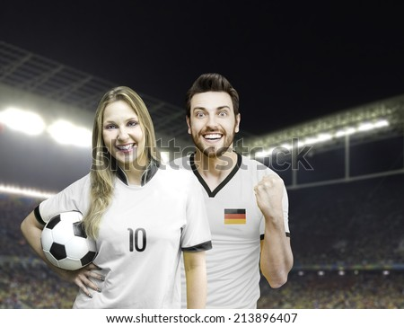 German couple soccer fan holding a soccer ball in the stadium