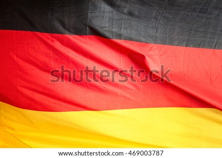 German flag. Wavy black, red, gold fabric background