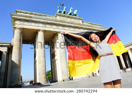 German flag - Woman happy at Berlin Brandenburger Tor cheering celebrating waving flag by Berlin Brandenburg Gate, Germany. Cheerful excited multiracial woman in Germany travel concept. - stock photo
