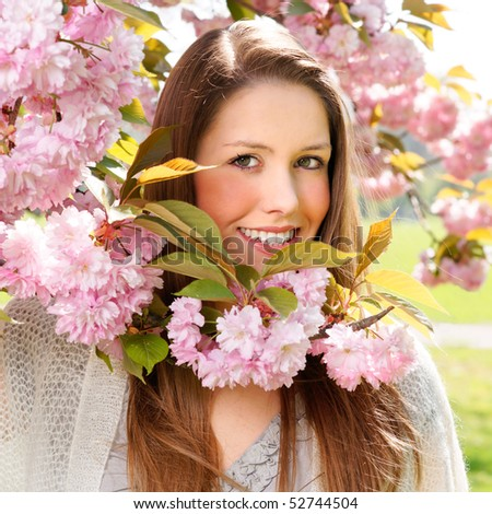 German girl standing behind cherry tree in the park.