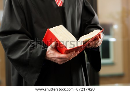 German Lawyer with civil law code in a court room, close-up, only torso to be seen