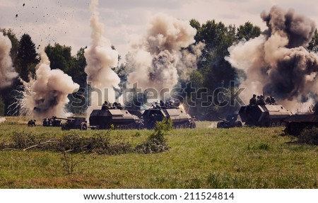 German medium half-track armored personnel on the field in the smoke and explosions of shells