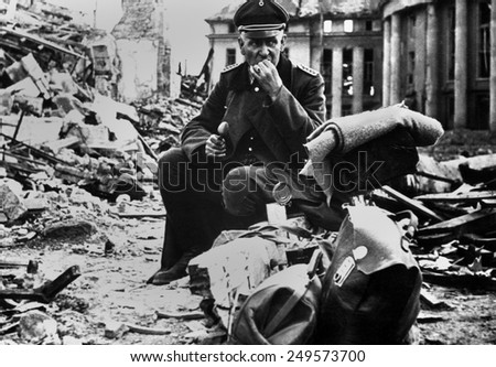 German Officer POW eating a can of U.S. C-rations, in the ruins of Saarbrucken. March 1945, during World War 2. - stock photo