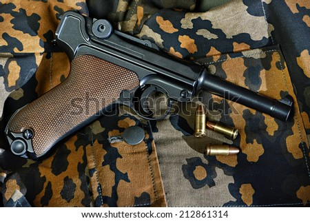 German Parabellum pistol with cartridges on camouflage uniforms - stock photo