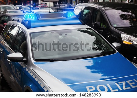 German police car standing with blue lights on a city street with passing cars