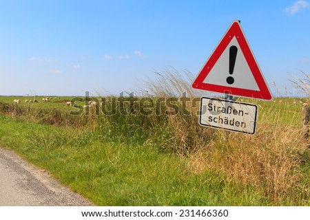 German road sign in the countryside warning of road damage - stock photo