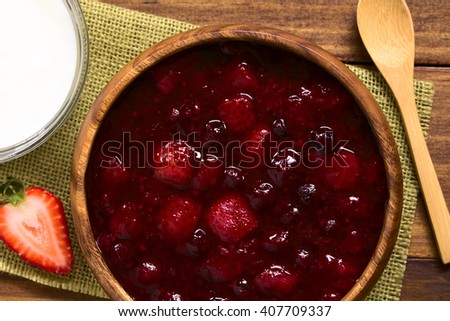German Rote Gruetze (red groats) red berry pudding made of strawberry, blueberry, raspberry and redcurrants cooked with sugar and starch, photographed overhead on wood with natural light