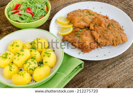 German schnitzel with potatoes, onion and lemon